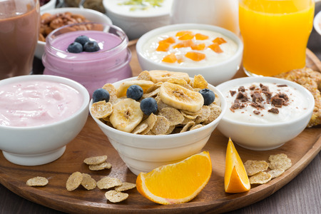 rich breakfast buffet with cereals, yoghurt and fruit on wooden tray, close-up