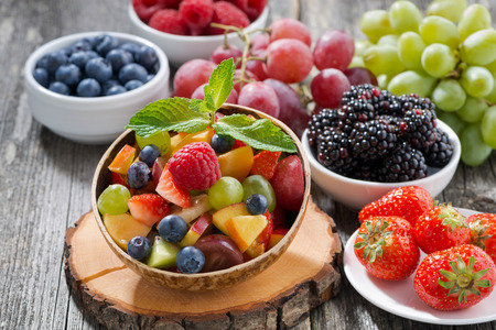 Photo for fruit salad in a bamboo bowl and fresh berries, horizontal - Royalty Free Image