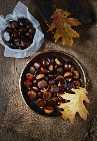 Roasted chestnuts in pan on rustic wooden background