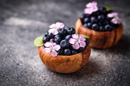 Fresh ripe blueberries in wooden bowl