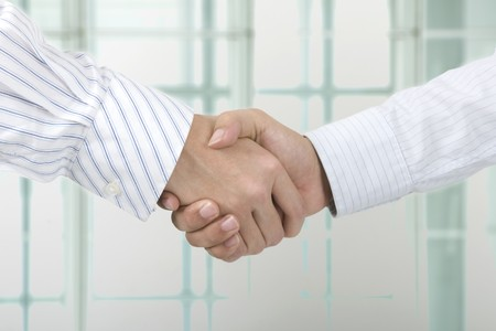 close up face shot of business hand shake