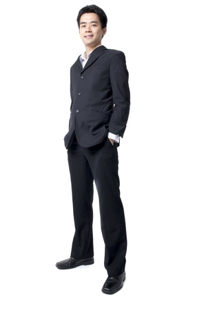 Full body of a smiling young Asian executive standing against isolated white background