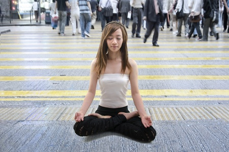 asian girl relaxed in the middle of a busy street in hong kong, focus on the girl