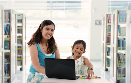mother and daughter with laptop learning inside a library, indian south asian people