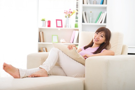 Photo for Beautiful smiling Asian woman with tablet computer. Lying on sofa   - Royalty Free Image