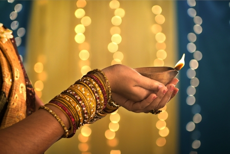 diwali festival of lights , hands holding indian oil lamp