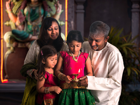 indian family celebrating diwali ,fesitval of lights inside a temple