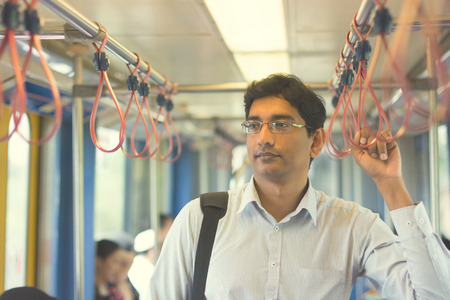 Asian Indian business man taking ride to work, standing inside train.