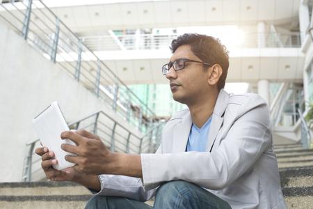Photo pour indian male using tablet outdoor - image libre de droit