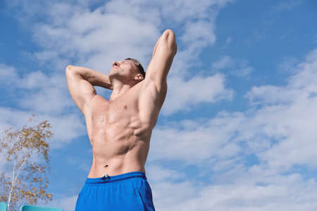 Foto de middle aged toned body man stands shirtless under sunlight and getting rest after workout. outdoors sport and active lifestyle. muscular caucasian man with toned abs relaxing on open air sportsground. - Imagen libre de derechos
