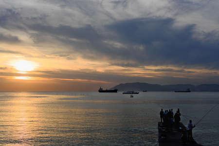 Photo pour sunset on a sea. unrecognizable fishermen catching fish in a dusk deep blue and orange shades of sunset. - image libre de droit