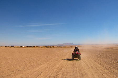 a couple in love travels through the desert on a Quad bike