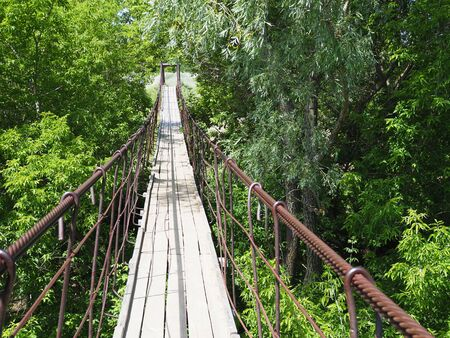 Photo for suspended wooden bridge over the river in the forest. - Royalty Free Image