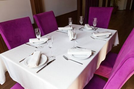 Photo pour Table setting for the holiday, white tablecloth dishes and appliances on the table in the restaurant hall with purple chairs - image libre de droit