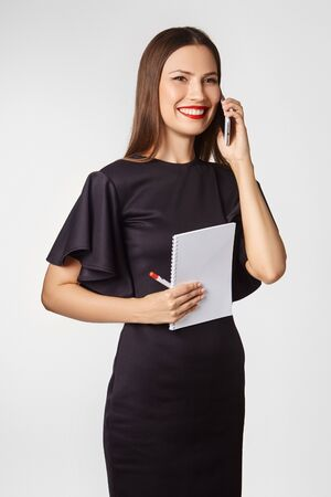 Photo pour Beautiful girl with dark hair, dressed in a black elegant dress in a business style in the studio on a white background. Talking on the phone and holding a notebook. - image libre de droit
