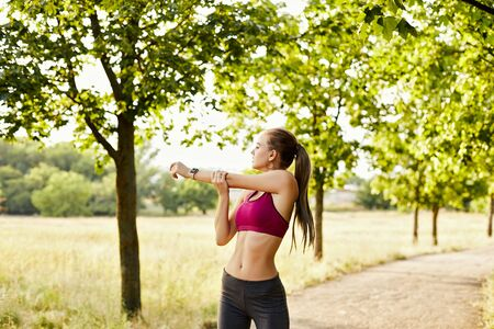 Photo pour Beautiful blonde healthy girl wearing sportswear doing exercises in the park on a summer evening - image libre de droit