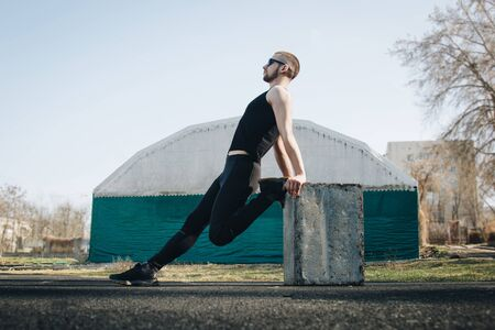 Photo for A slender young man in black clothes and sunglasses is exercising outdoors. fitness athlete on the sports field. training with projectiles. warm up stretching legs. body preparation for the summer. - Royalty Free Image