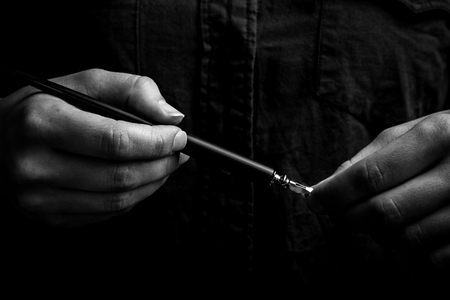 Photo pour female hand elegantly holding an ink pen with a metal tip close-up on a black background. classic fountain pen isolated macro black and white. copy space. - image libre de droit