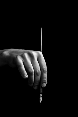Photo pour female hand elegantly holding an ink pen with a metal tip close-up on a black background. classic fountain pen isolated macro black and white. copy space. vertical. - image libre de droit