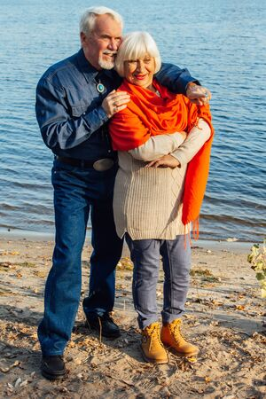 Photo for cheerful senior citizens woman and man are standing and hugging on the lake, against the background of the bridge - Royalty Free Image