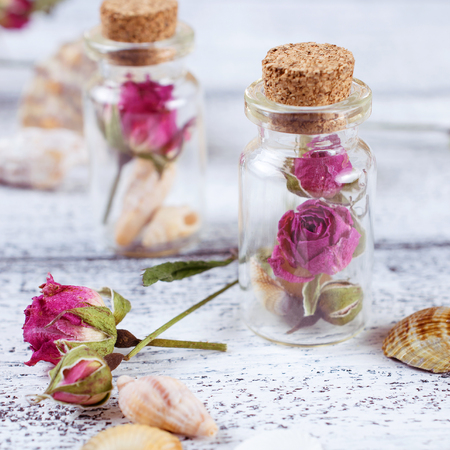Small glass bottle filled dry roses and seashells on the worn wooden boards
