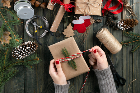 Photo for Christmas workshop theme. Top view of woman hands wrapping New Year present and tie bow. Packed gifts and scrolls, spruce branches and tools on shabby wooden table. - Royalty Free Image
