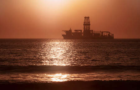 Photo pour A large vessel on horizon in the atlantic ocean under the bright sun and red sunset.  Sunlight reflection off the water - image libre de droit