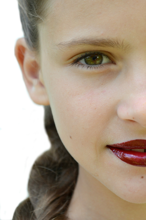 Half face of a young girl with a turquoise sheen on lips