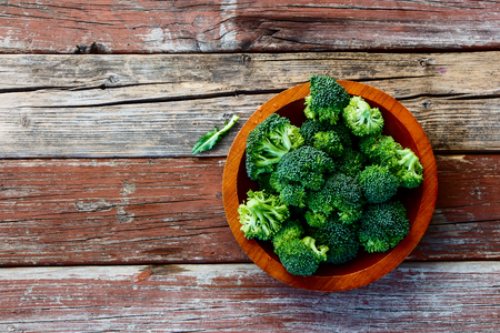 Fresh green broccoli in wood bowl over rustic wooden background - healthy or vegetarian food concept  Top view.