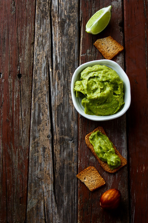Top view of Freshly Homemade Guacamole with bread toast on rustic wooden texture. Copy space.