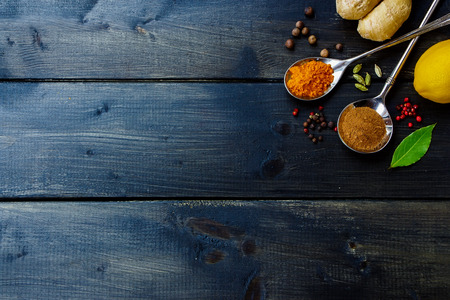 Top view of various herbs and spices selection on dark wooden table. Background with space for text.
