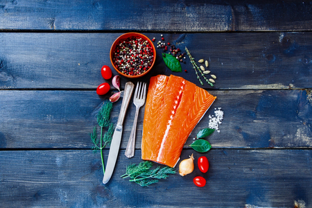 Foto de Food background with fresh salmon fish on dark wooden board. - Imagen libre de derechos