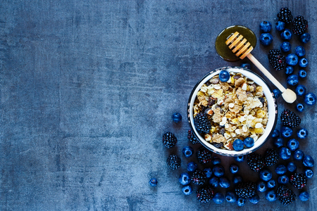 Granola in vintage mug, dark berries and honey for delicious breakfast on grunge background with space for text on left, top view.