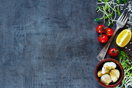 Photo pour Top view of ingredients for cooking (tomatoes, garlic, pepper, lemon, salad leaves, olives, olive oil) on dark old background. - image libre de droit
