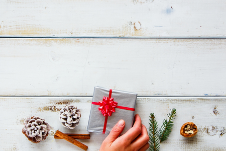 Christmas composition. Woman hand holding christmas gift on white wooden background. Christmas, winter, new year concept. Flat lay, top view, copy space