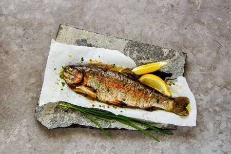 Photo pour Flat-lay of Baked Trout Fish with Herbs and Lemon, top view - image libre de droit