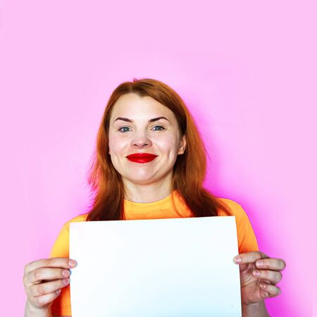 Photo for Redhead girl is holding white mockup blank on pink background - Royalty Free Image