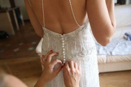 Foto de bride dress charges corset tie help hands girlfriend - Imagen libre de derechos