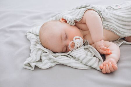 Photo pour newborn baby sleeps with a dummy in the bedroom covered with a small blanket - image libre de droit