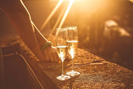 Foto de couple in love with glasses wine romance on the roof of the building sunset - Imagen libre de derechos