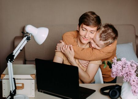 Photo pour love baby son to mom working on a laptop hugs and tenderness of family relationships - image libre de droit