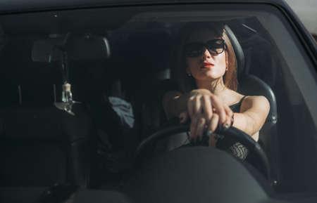 Photo pour fashion stylish girl in sunglasses driving a car lifestyle - image libre de droit