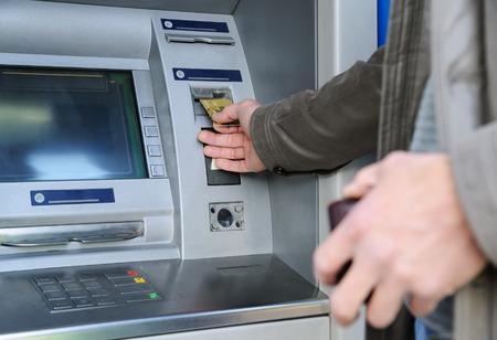Photo pour A man is inserting a bank card into an ATM. - image libre de droit