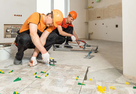 Photo for Two workers are installing ceramic tiles on the floor. - Royalty Free Image