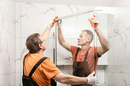 Photo for Workers are installing glass door of the shower enclosure. - Royalty Free Image