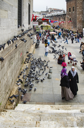 Istanbul, Turkey - March 29, 2013: New Mosque (Yeni Cami) People and pigeons around the courtyard. It is situated on the Golden Horn, at the southern end of the Galata Bridge, and is one of the famous architectural landmarks of Istanbul.