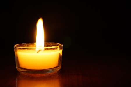 Candles light flame on dark background.