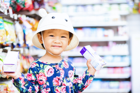 Foto per Sweet Asian girl shopping in mini mart with basket, enjoy buying thing in mart - Immagine Royalty Free