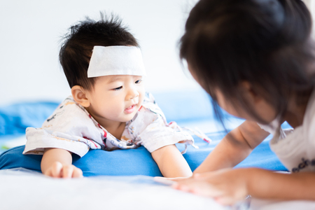 Photo pour Unhappy Asian little baby child sick with cool fever jel pad on forehead - image libre de droit