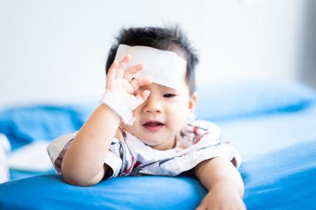 Foto de Unhappy Asian little baby child sick with cool fever jel pad on forehead - Imagen libre de derechos